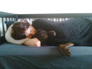 human_sleeping_on_a_bed_with_a_dog